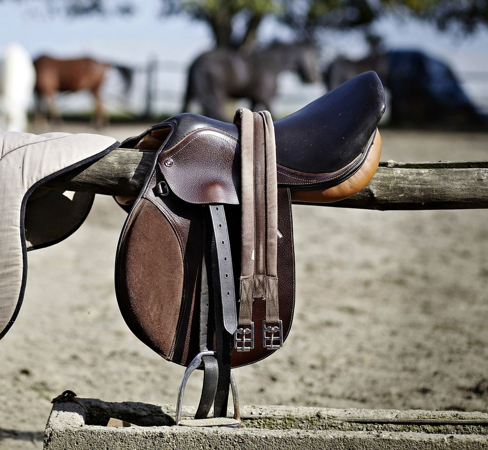 A saddle with a synthetic girth hanging on a fence rail.