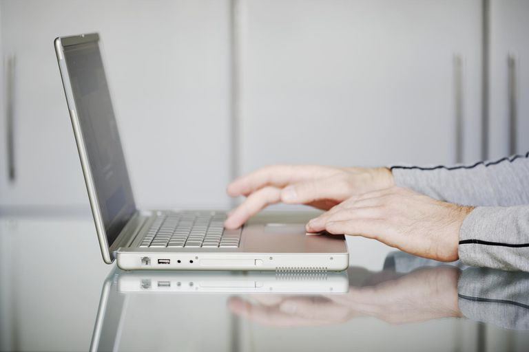 Picture of a man typing on a laptop computer