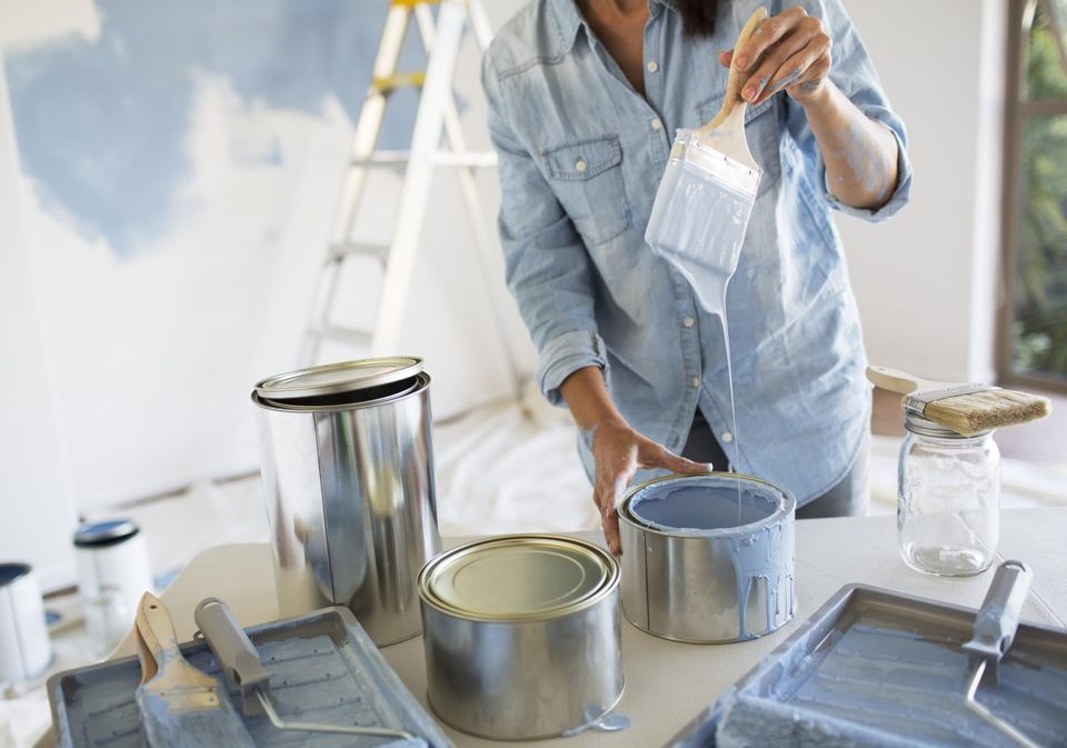 Woman holding paintbrush with blue paint