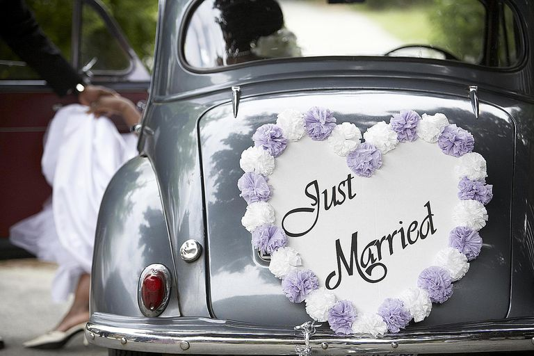 """A couple enters a vintage car with a """"just married"""" sign after their wedding."""