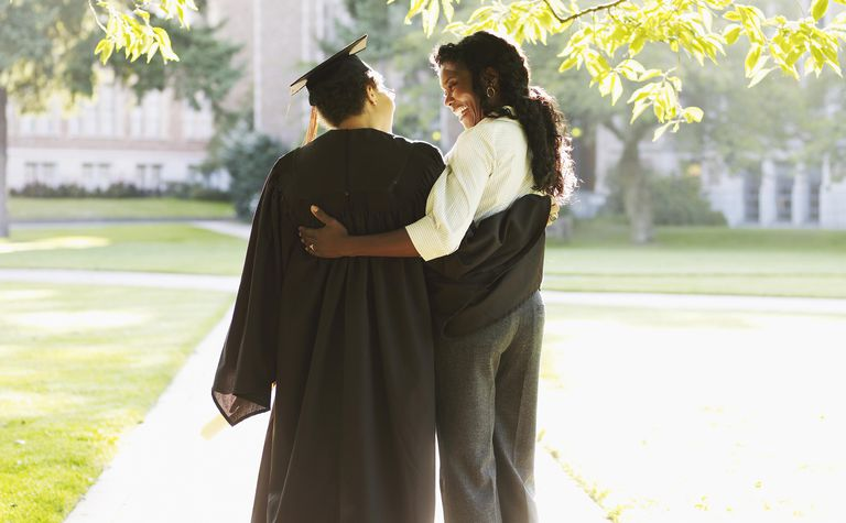 Mother and daughter in graduation gown hugging on campus, rear view