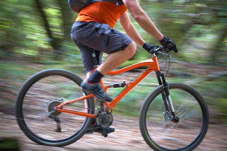 man on mountain bike riding fast through