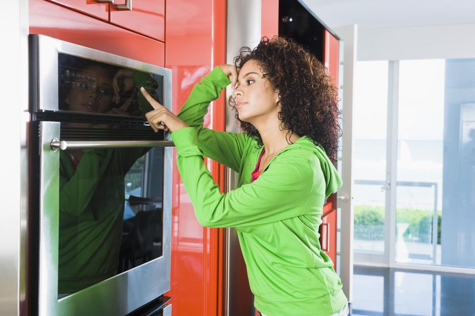 Woman leaning against an oven in the kitchen