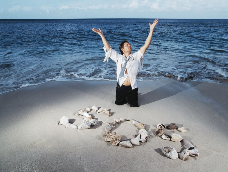 A man stranded on a beach next to an SOS sign made from rocks