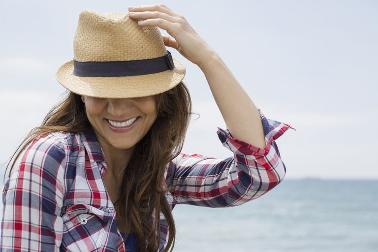 Smiling woman wearing hat with ocean in background