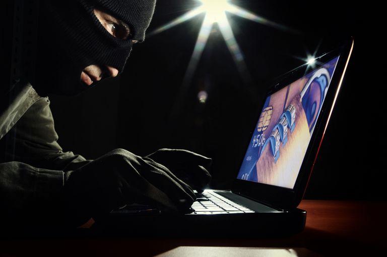 man in ski mask on laptop