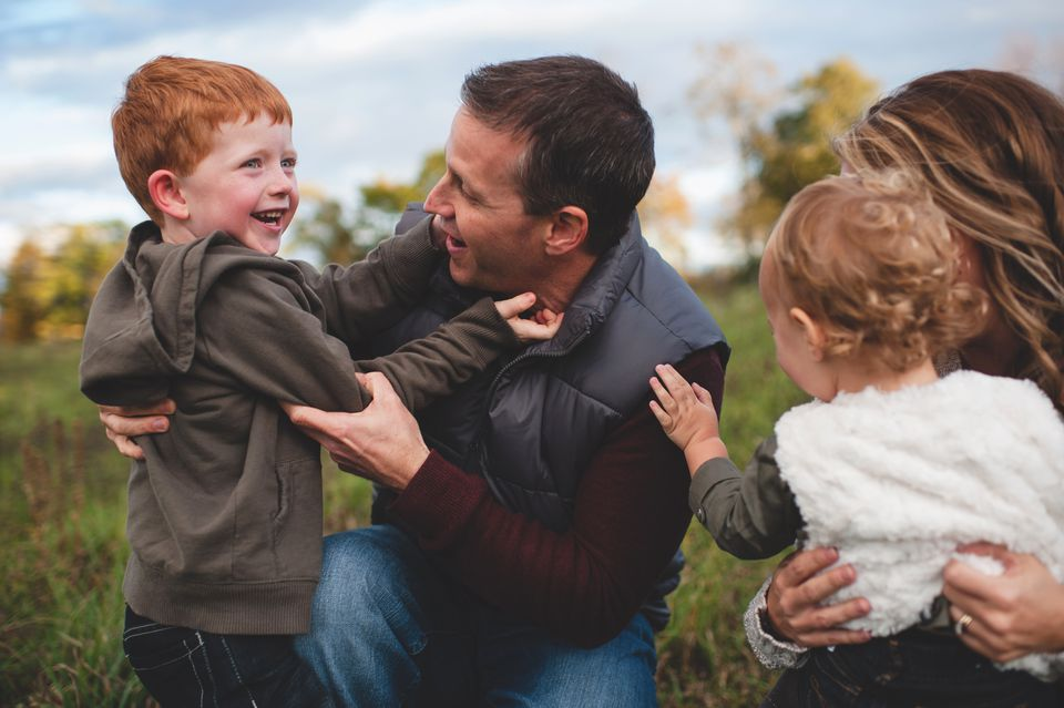 Mid adult couple with two young children in field