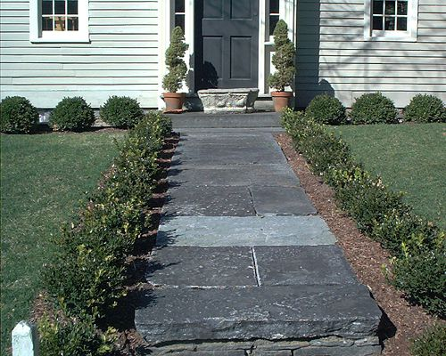 Granite pathway lined with boxwood shrubs.