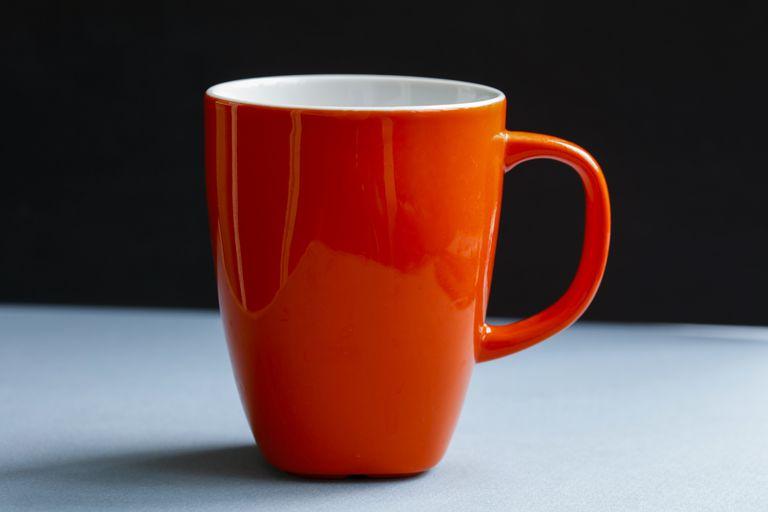 Orange coffee cup on black background
