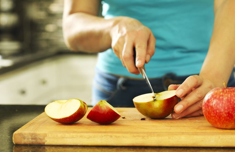Woman cutting fresh apples