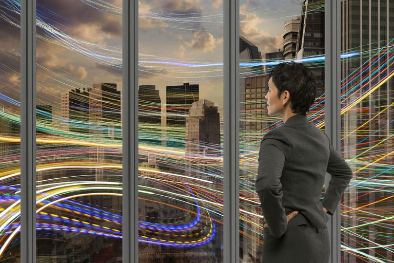 Businesswoman staring out the window with data moving by