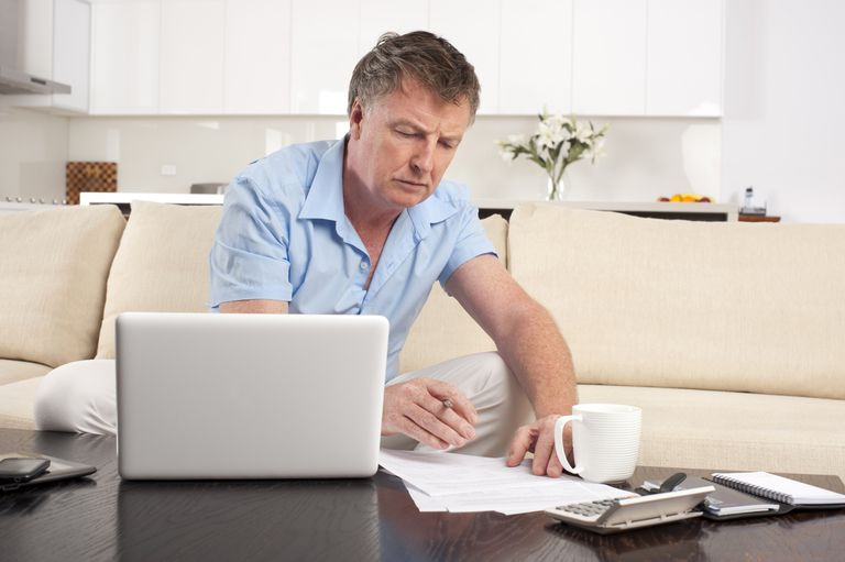 Worried Mature man doing paperwork with laptop