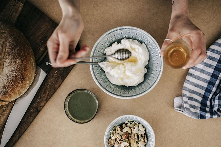 woman eating yogurt with honey