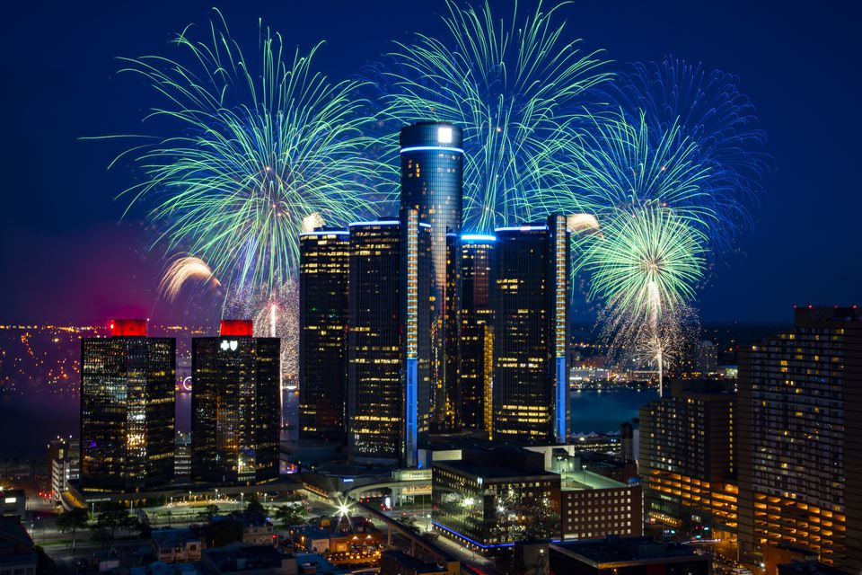 This image, shot from a rooftop, shows Detroit's Renaissance Center / GM Headquarters, silhouetted by a burst of fireworks over the Detroit River.
