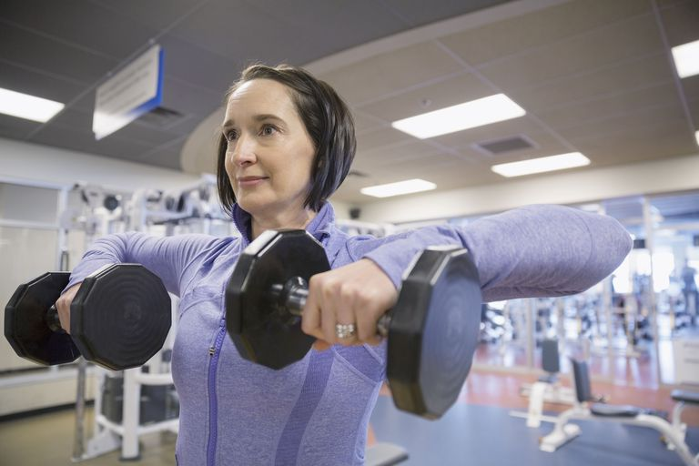 woman doing upper body working in gym with dumbbells