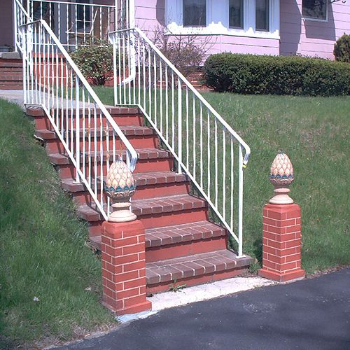 Brick steps up a slope leading to a front door.