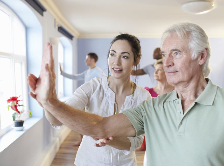 older man getting instruction at tai chi class