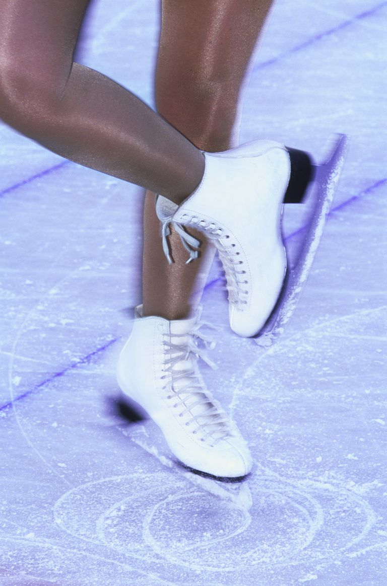 Blurred view of a woman skating with white ice skates