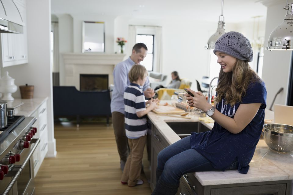 Girl texting with cell phone on kitchen island
