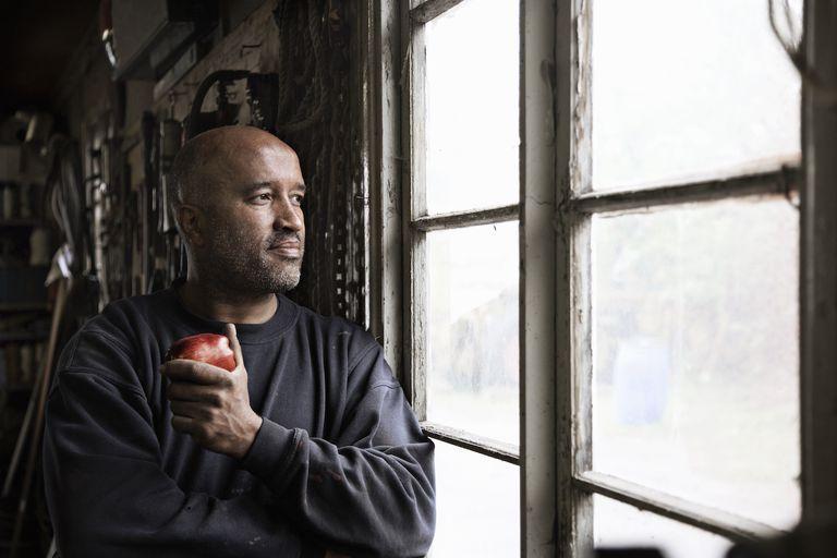 Man eating apple in workshop