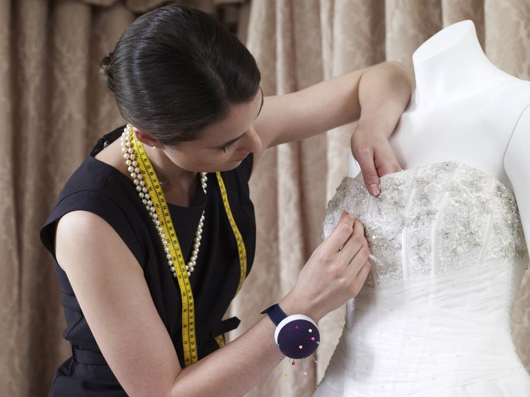 Designer making adjustments to wedding gown