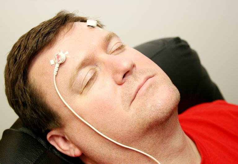 Man with biofeedback electrodes on head
