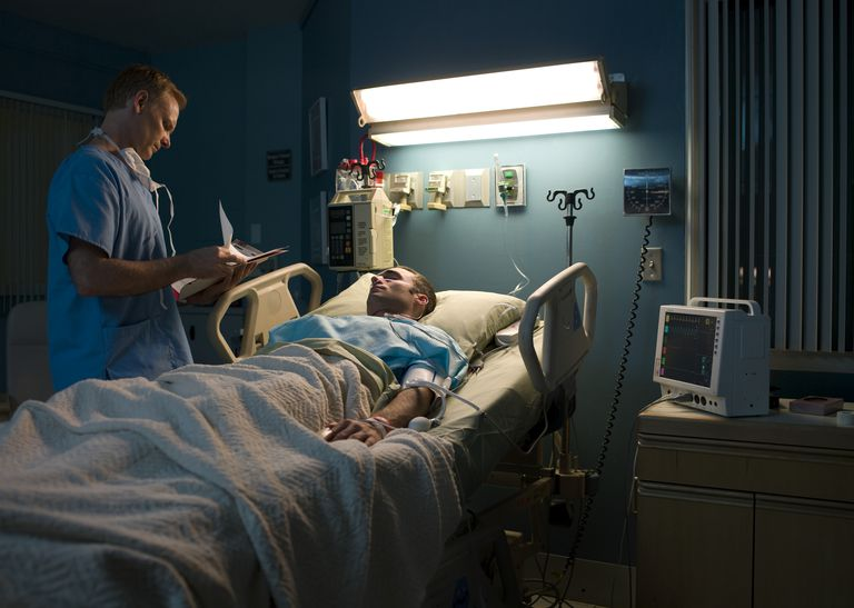 Doctor visits patient bedside at night in hospital
