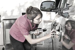 Insurance adjuster inspecting damage to vehicle
