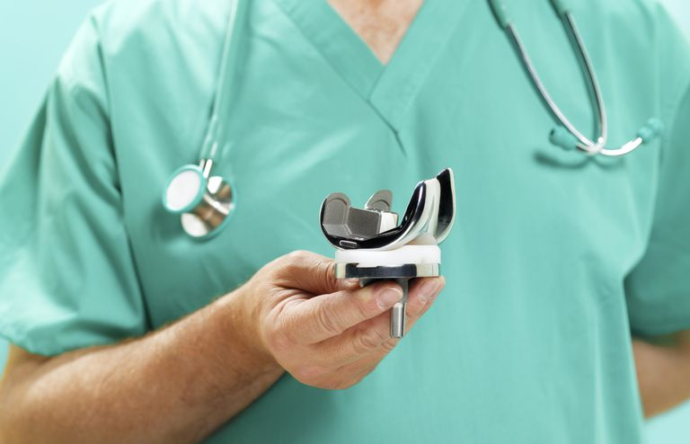 doctor holding knee replacement implant