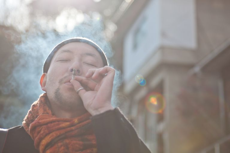 Asian man smoking, Japanese male smokers are less likely to get lung cancer