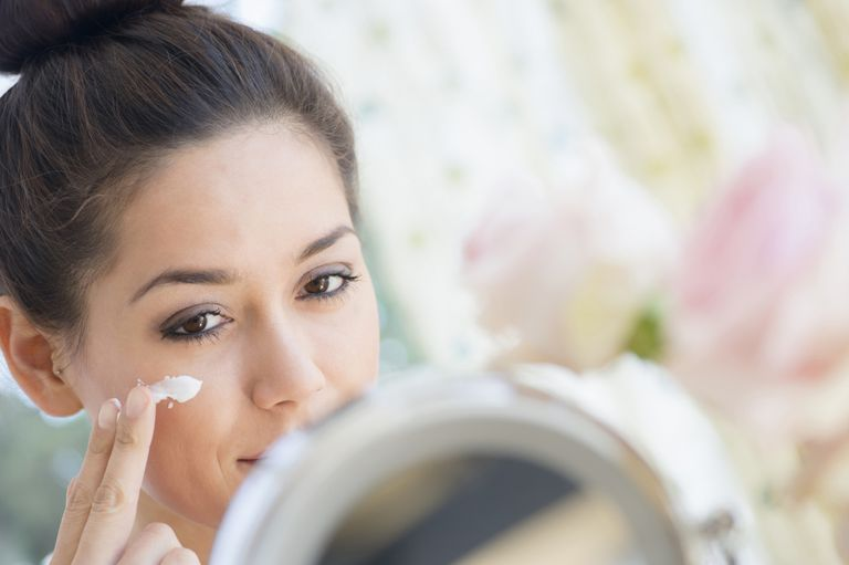 A woman applying moisturizer in the mirror