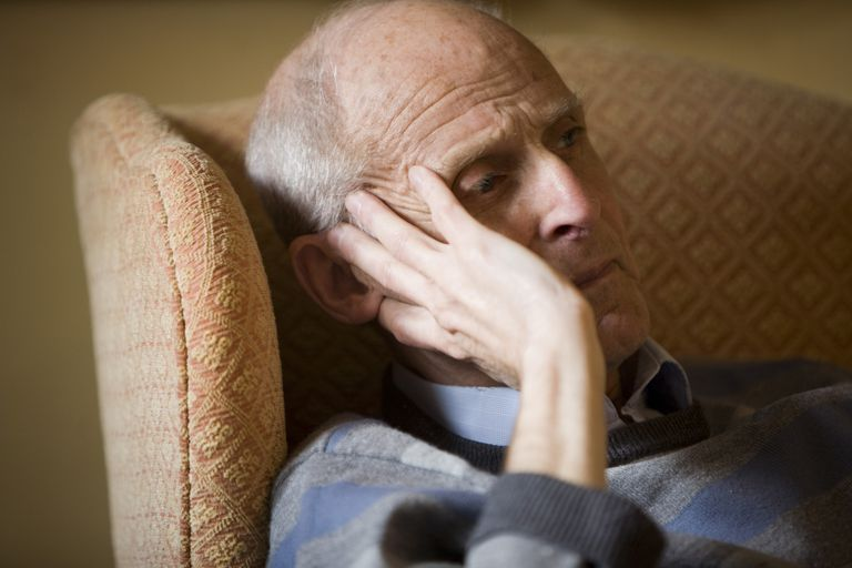 Older man sitting in chair and looking off into the distance