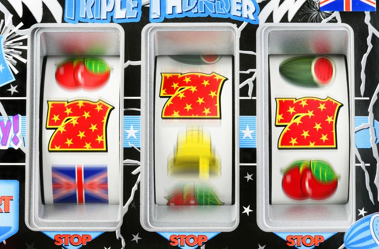 Fruit machine bars spinning to line of 7's, close-up (blurred motion)
