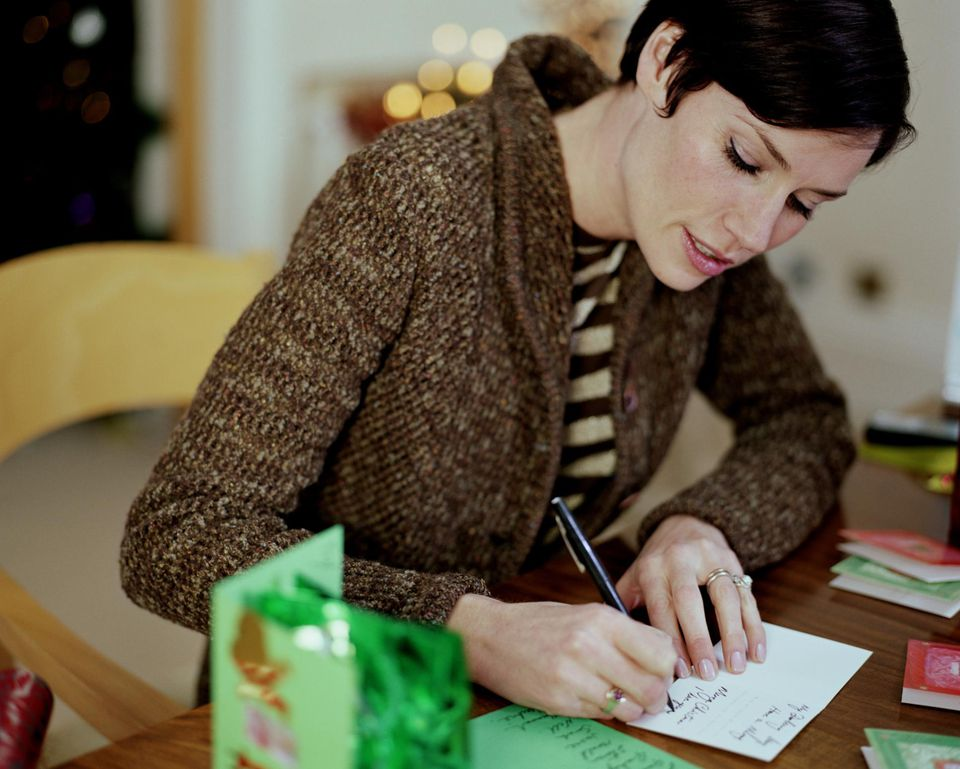Woman sitting at table writing christmas cards