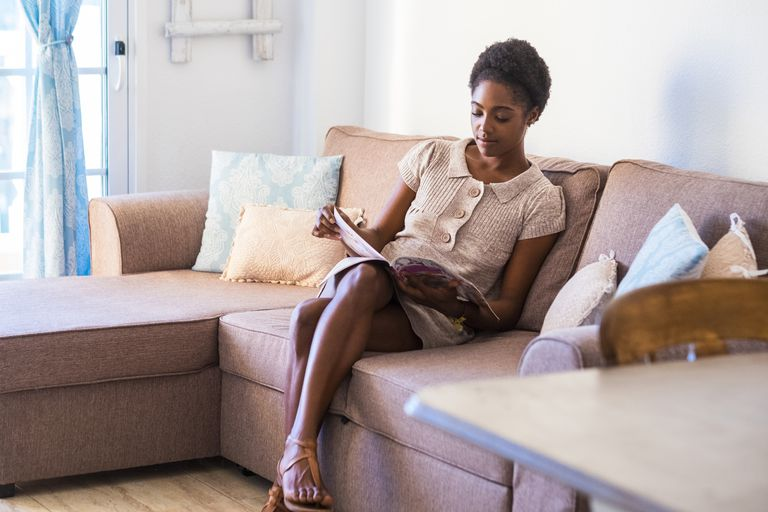 Young woman sitting on the couch reading magazine