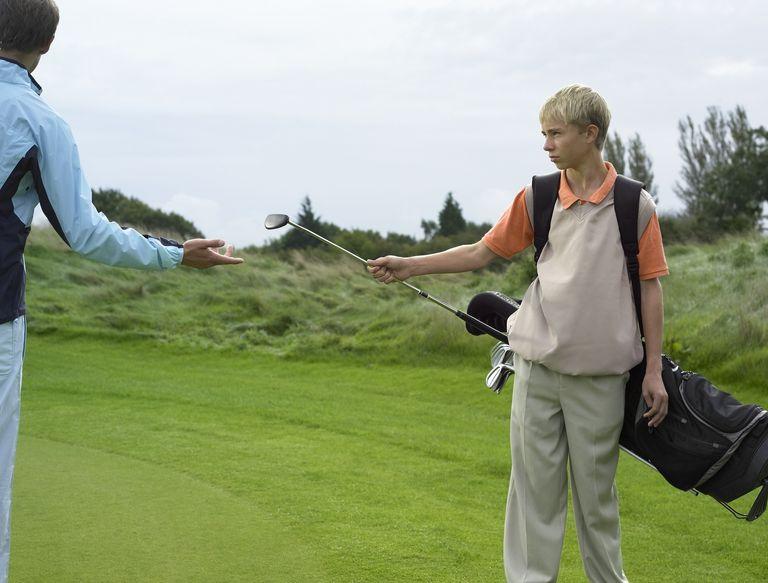 Male teenage caddy (13-15) giving golf club to man