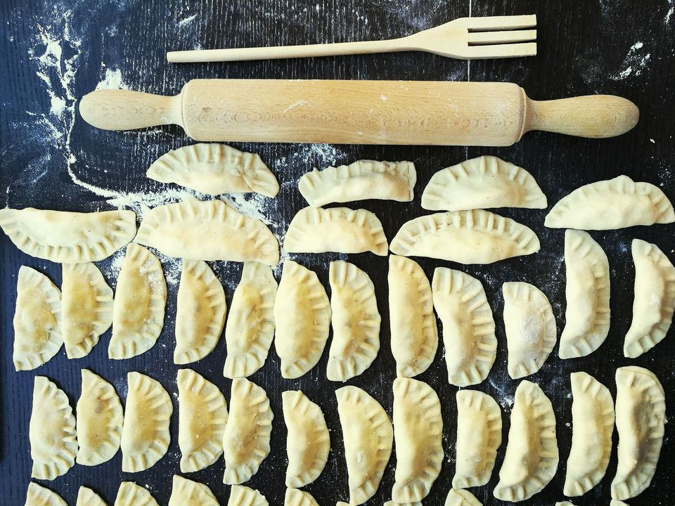 overhead shot of pierogis and a rolling pin on a counter