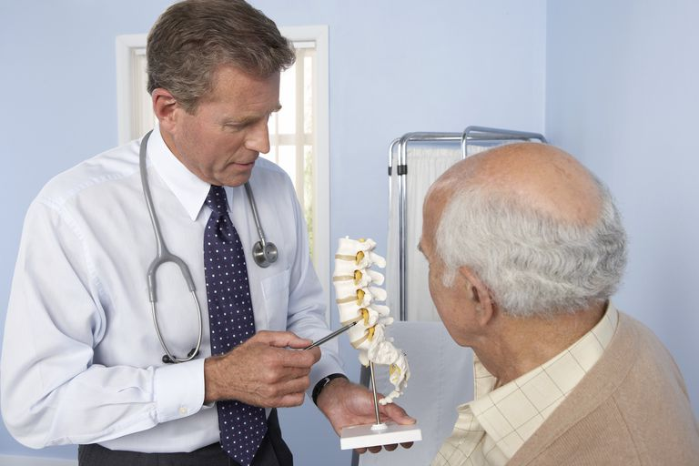 Medical consultation, general practitioner refers to model of spine while discussing elderly patient
