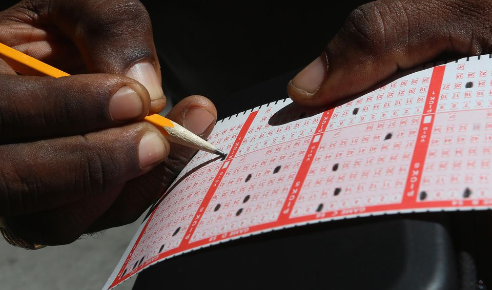 Anthony Adams fills out his numbers while waiting to purchase Powerball tickets in Manhattan on May 17, 2013 in New York City.