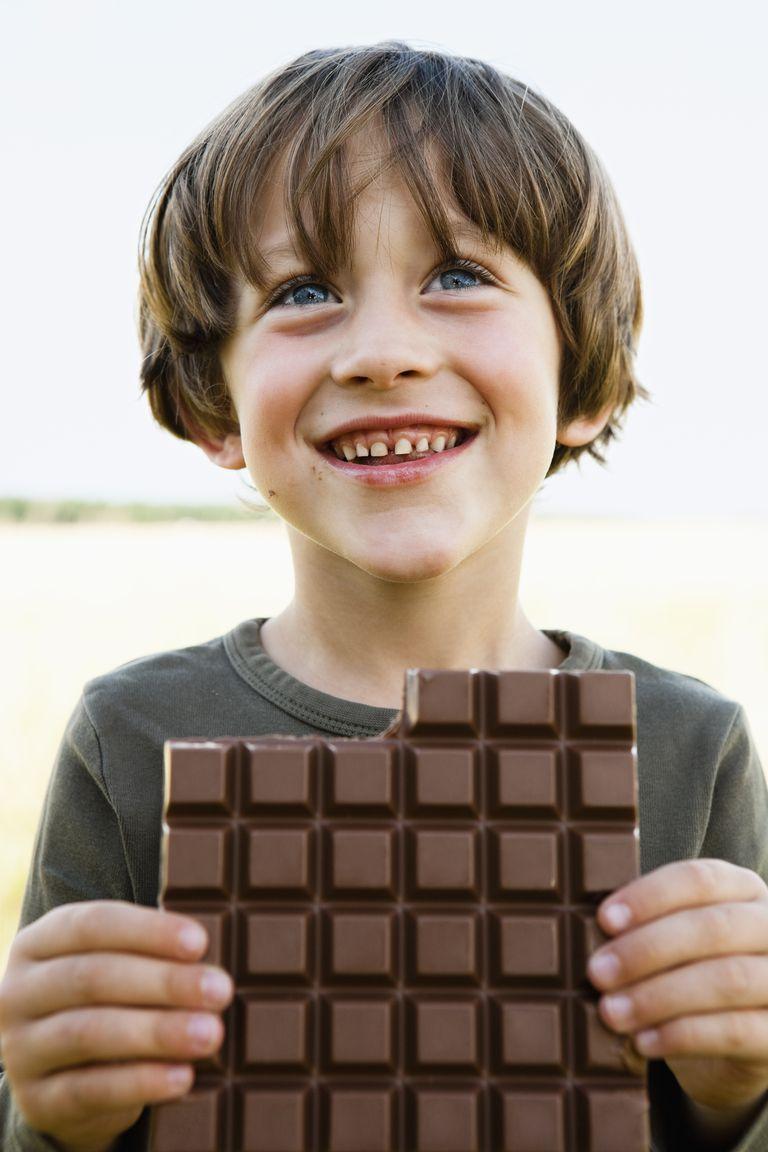 A boy eating a huge bar of chocolate