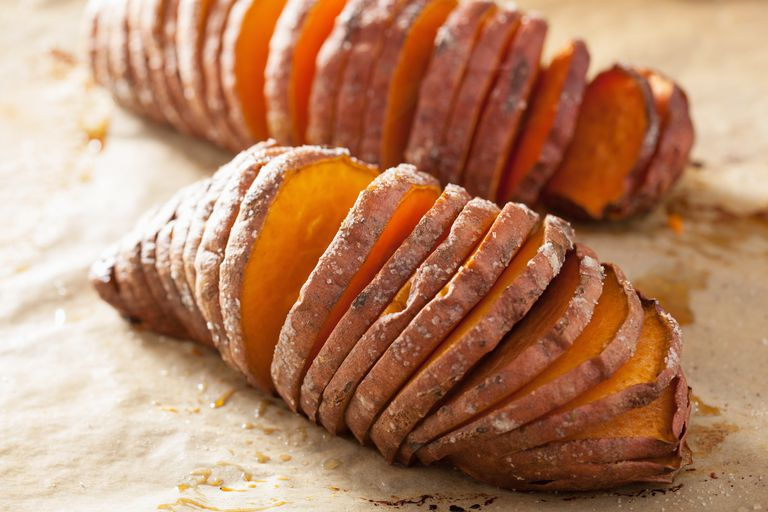 sliced baked sweet potatoes on parchment paper
