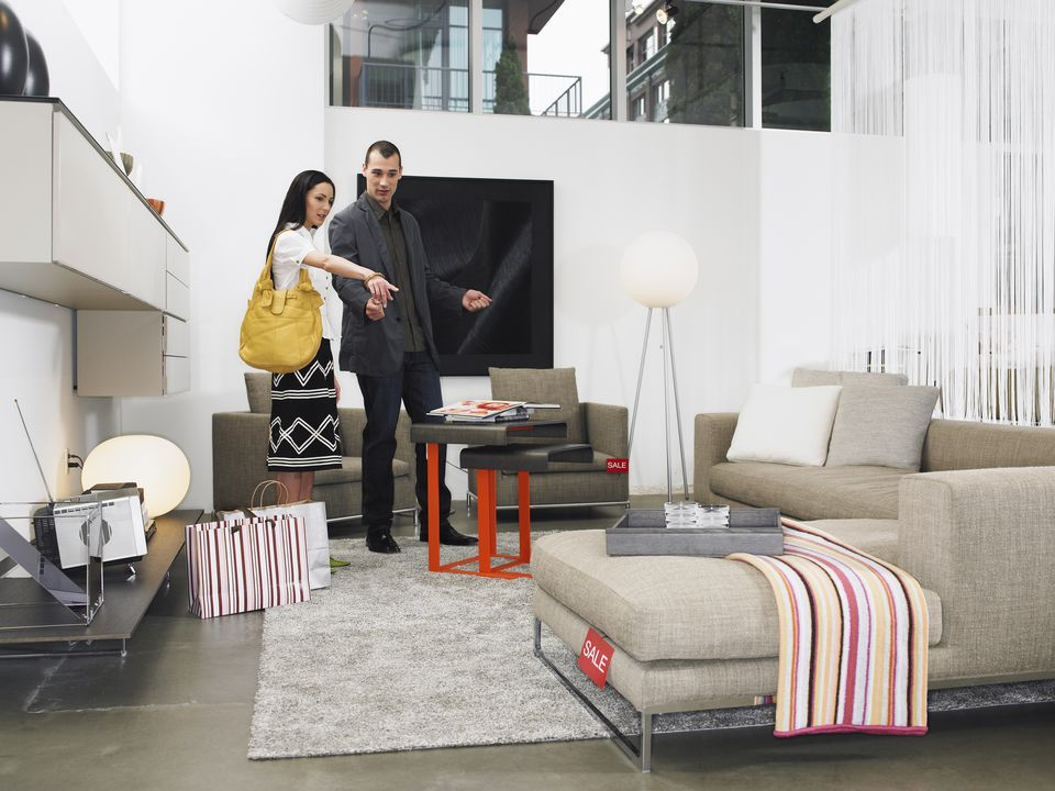 Young couple looking at sofa in furniture store