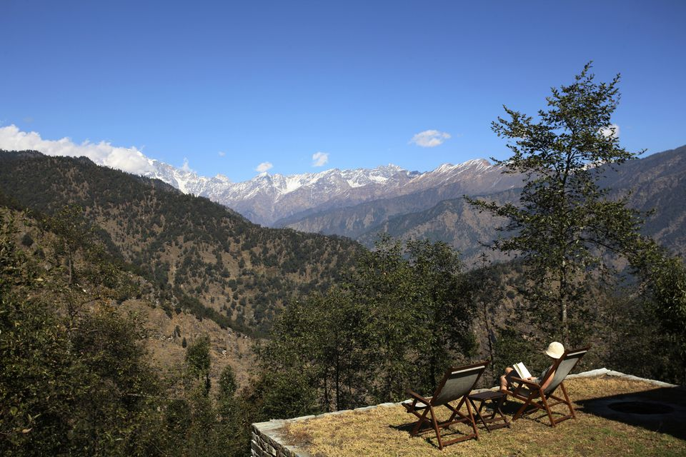 A tourist sits reading a book with a view of the Indian Himalayas
