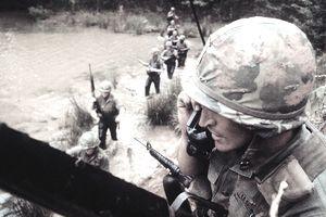 Officer talking on radio phone as line of soldiers crosses river below him