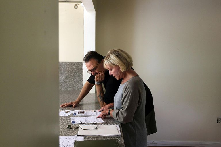 couple looking at house listings on counter