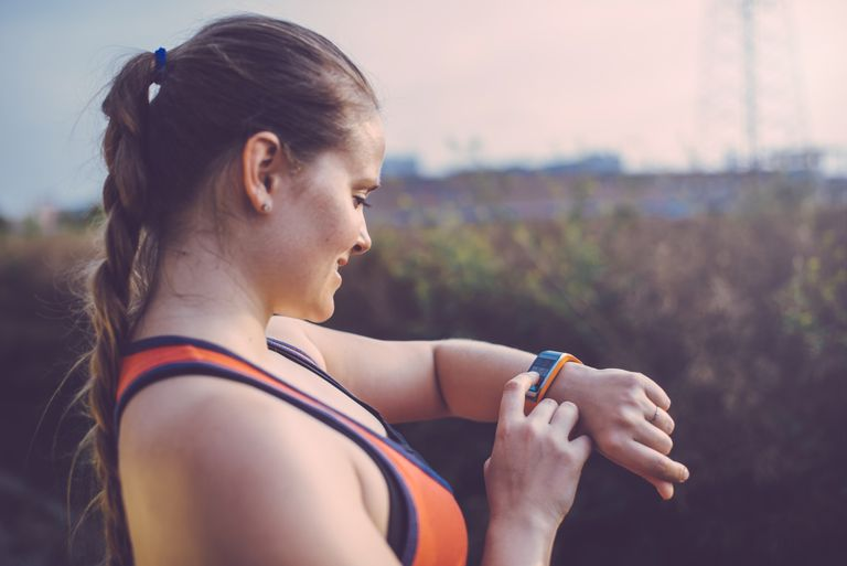 woman runner checking wrist tracker