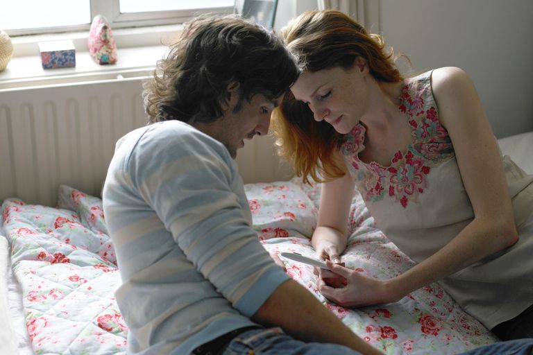 Couple lying on bed looking at pregnancy test.