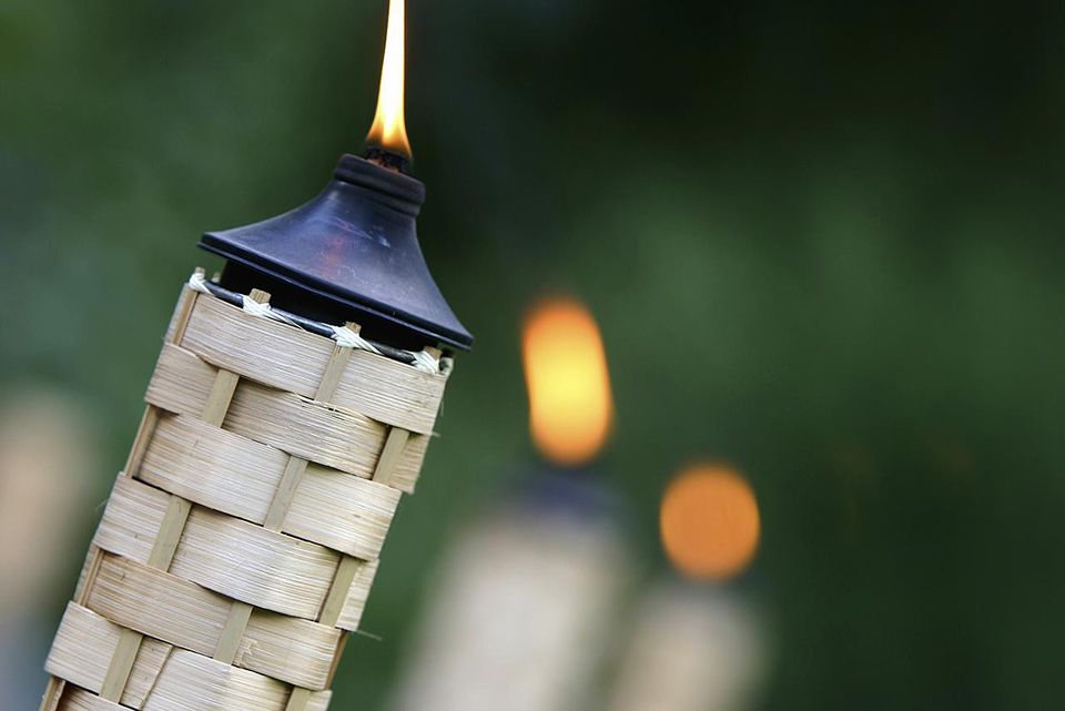 Row of lit tikki torches, focus on front torch