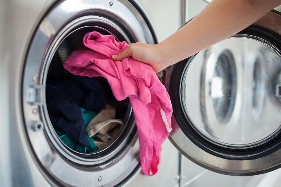 Woman taking shirt out of the dryer