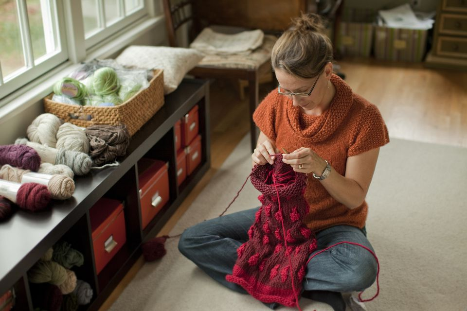 Woman knits a beautiful scarf in her living room.